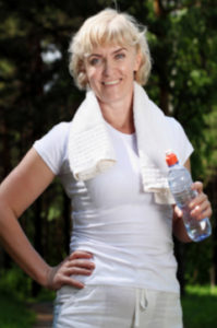 older woman drinking water after exercise